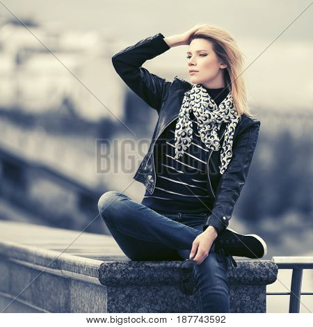Happy young fashion woman in city street. Stylish female model in leather jacket outdoor