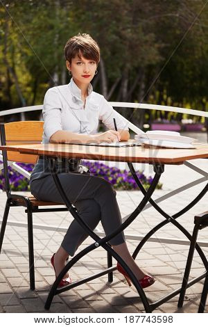 Young fashion business woman working at sidewalk cafe. Stylish female model in white blouse