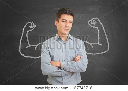 Strong and self confident businessman with chalk muscles on blackboard behind him