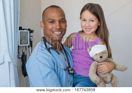 Happy male nurse carrying cute girl in hospital room. Doctor with stethoscope and little patient looking at camera in a medical clinic. African man with young child patient smiling after medical exam.