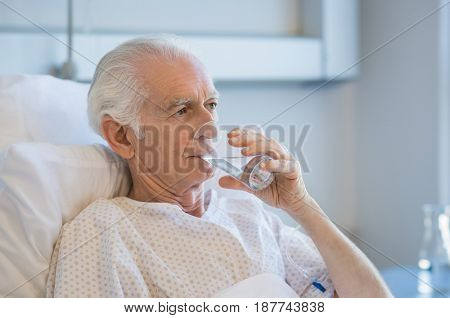 Senior patient in hospital drinking water. Old man recovering from disease in hospital drinking water after taking medicine. Aged man admitted to hospital resting on bed.