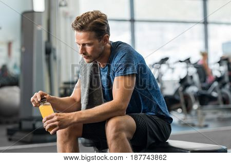 Young man in gym sitting alone opening a bottle of energy drink. Thoughtful fit man in gym holding fruit juice and thinking. Tired man in gym resting while drinking fruit juice.