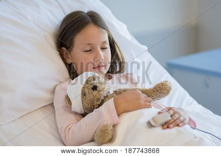 Cute girl sleeping in hospital bed with teddy bear. Little girl resting in hospital while hugging her teddy bear. Ill child at medical clinic.