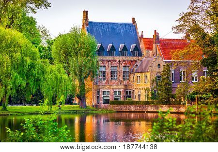 Vintage building over lake of love in Minnewater park in Bruges Belgium near Beguinage monastery of Beguines. Picturesque landscape with green trees sunset time.