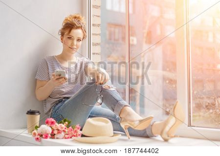 Young trendy woman by the window. A hipster style girl with a phone and coffee in fashion glasses sits alone on a windowsill