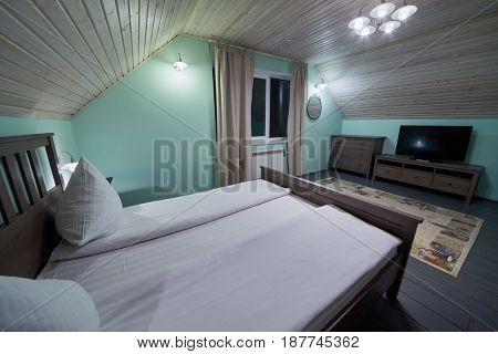 Interior of room with double bed, carpet, tv set in hotel.