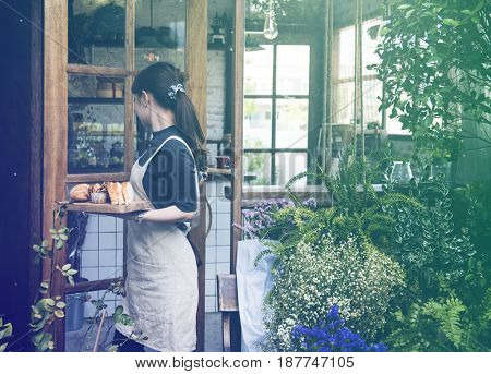 Young woman carrying bread pastry to customer