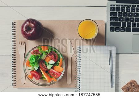 Healthy business lunch in office top view, vegetable salad bowl with wooden cutlery on white wooden desk and notepad with pen.