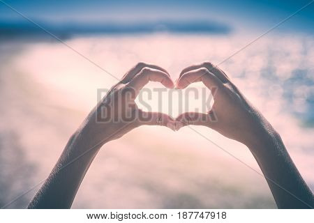 Young wooman's hands in heart shape showing love friendship on blurred sea background. Instagram stylisation.