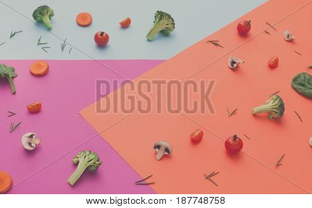 Diet, detox and healthy food background flat lay of fresh organic raw vegetables on abstract bright papers. Ingredients for salad - broccoli, mushroom, carrot, cherry tomato, spinach