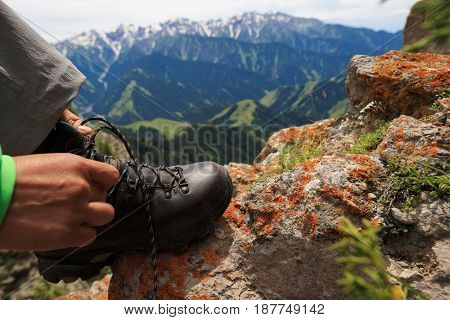 Woman hiker tying shoelace on mountain top