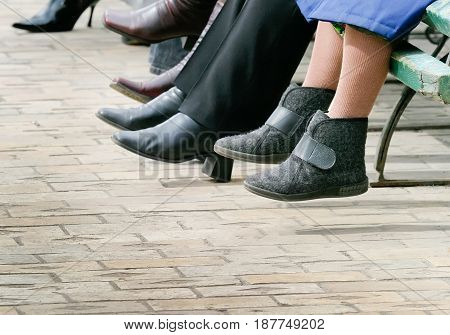 Spring, people are sitting on the bench and resting. In the frame, legs and shoes.