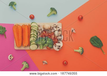 Wooden board with cut organic raw vegetables on bright geometric background. Healthy food, copy space. Ingredients for salad or soup - mushroom, cherry tomato, broccoli, cucumber, carrot