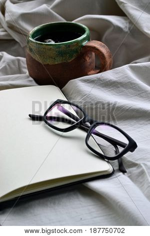 Notebook with glasses and a cup of tea in bed