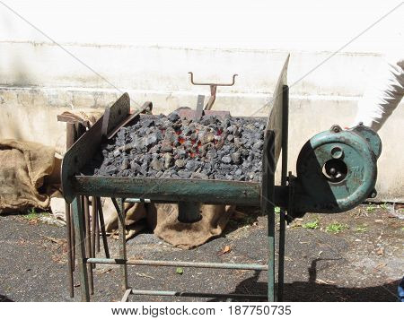 Old-fashioned blacksmith furnace with burning coals for iron work . Photo taken during outdoor public event (no ticket required) in public place . Pistoia Italy