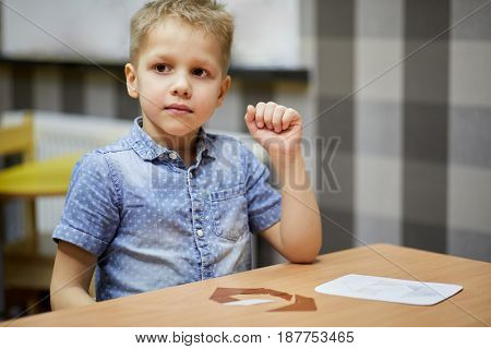 Little boy sits at desk with paper puzzle.
