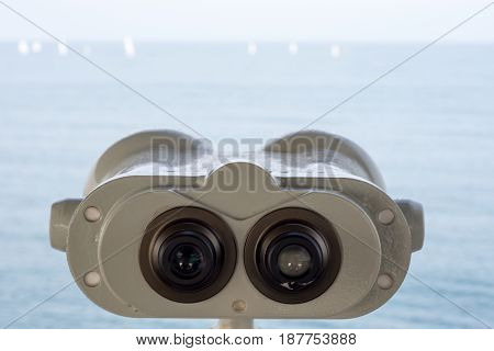 Binoculars Pointing Out to Sea and Sailing
