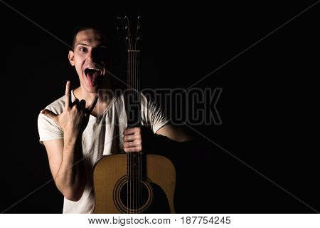 Guitarist, Music. A Young Man Stands With An Acoustic Guitar And Shows His Tongue And Fingers On A B