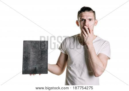 A Young Handsome Guy With An Empty Gray Plank, Looks Surprised At The Shot. Place For Signature, Tex