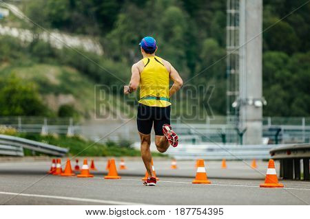 back male athletic runner running in roads with traffic cones safety