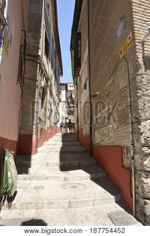 GRANADA, SPAIN - MAY 20, 2017: People descending by a narrow street in in the quarter of Albayzin that leads to the Darro way in Granada Andalusia Spain.