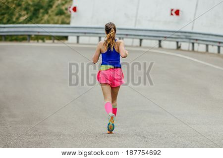 young woman runner in bright pink compression socks running on mountain road