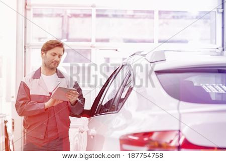 Male repair worker using tablet PC while standing by car in workshop