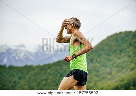 Rosa Khutor Russia - May 7 2017: old man runner on water point in hand sponge with water in race Spring mountain marathon