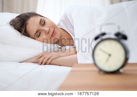 Beautiful young and happy woman sleeping while lying in bed comfortably and blissfully smiling.
