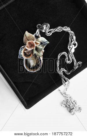 Vintage ceramic floral pendant in black jewel box closeup