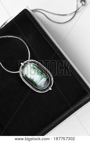 Vintage silver enameled medallion in black jewel box closeup