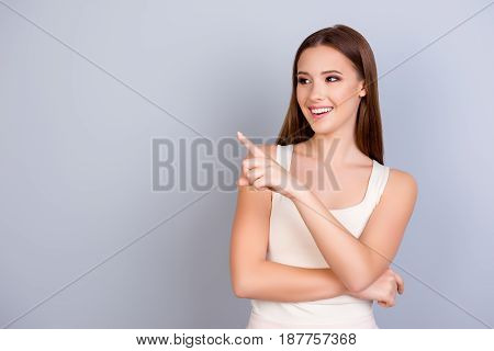 Cheerful Cute Model On Blue Background Is Pointing On A Copy Space, Wearing Casual Clothes, Smiling