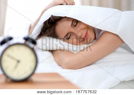 Sleepy young brunette woman stretching hand to ringing alarm willing turn it off. Early wake up, not getting enough sleep concept.