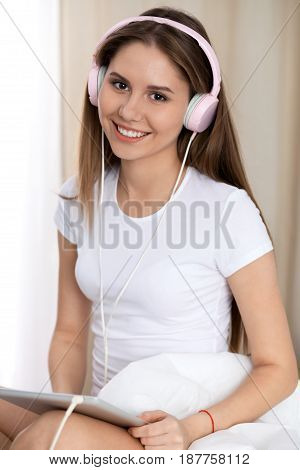 Woman listening music in bed with pink headphones after wake up, entering a day happy and relaxed after good night sleep. Sweet dreams, good morning, new day, weekend, holidays concept