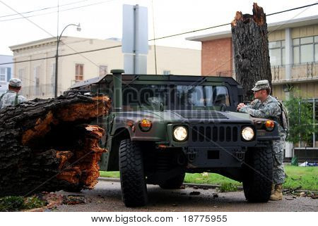 NEW ORLEANS - SEPT 1: A National Guardsman stands next to a Humvee as he inspects damage caused by a fallen tree on a street after Hurricane Gustav on September 1, 2008 in downtown New Orleans.