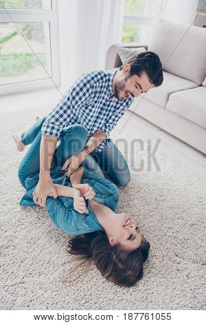 Excited Young Couple Is Fooling Around And Plays Indoors At Home, At A Cozy Beige Carpet, Wearing Ca