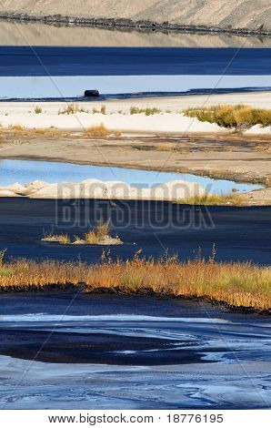 Alternating stripes of bitumen, water, sand and grass at a mine's tailings pond, where fine waste gradually settles. Also one oil barrel visible.