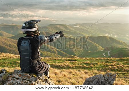 Male Professionally downhill rider Points with a finger at the landscape sits on a stone relaxing after a tense race next to his mountain bike