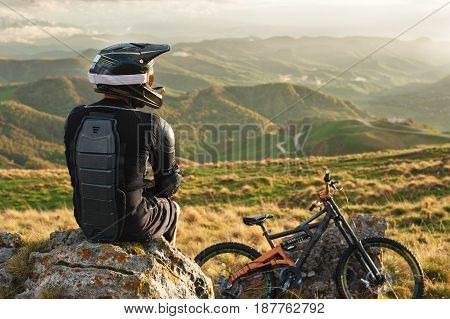 Male Professionally downhill rider sits on a stone relaxing after a tense race next to his mountain bike