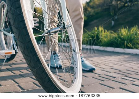 Wheel of a bicycle and female feet in sneakers close-up