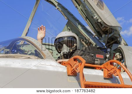 Military Pilot In Cockpit Jet Plane With A Raised Hand