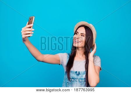 Young Cheerful Attractive Brunette  Is Smiling On The Blue Background. She Is Taking Selfie On The C