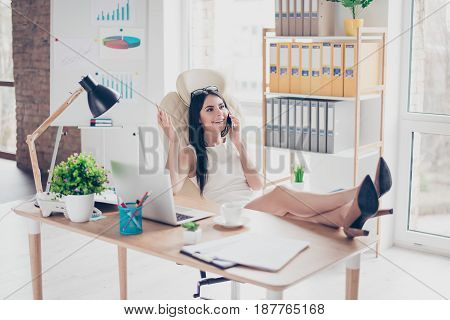Young Lady Is Resting At Her Work Place By Talking To A Friend On Phone, Putting Her Feet On The Des