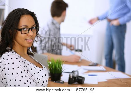 Business people meeting around table, focus on african american lady. Start up team