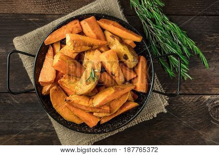 An overhead photo of roasted sweet potatoes in a pan, shot from above on dark rustic wooden textures with rosemary branches, with a place for text