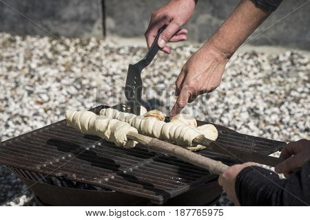 Homemade dough over a grill with hand ready to bake some bread in the summer