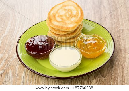 Green Plate With Pancakes And Bowls With Different Jams