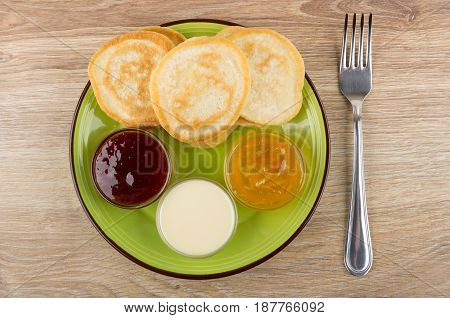 Green Plate With Pancakes And Bowls With Different Jams, Fork