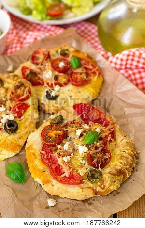 Mini pizzas with thick yeasted crust with tomato and feta cheese