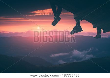 Hikers sit on a wooden flooring above the mountain valley and enjoy sunset. Instagram stylisation.